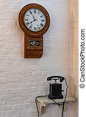 Antique wooden telephone and clock on white wall