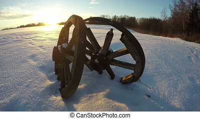 antique wooden wheels in the snow