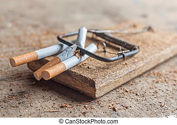 Antismoking background with broken cigarettes in a trap