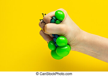 Antistress ball in the girl's hand, on a yellow background
