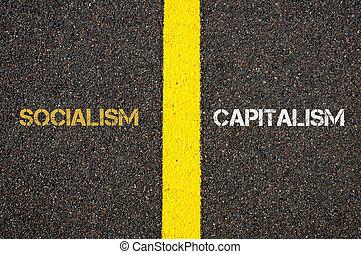 Antonym concept of SOCIALISM versus CAPITALISM written over tarmac, road marking yellow paint separating line between words