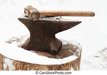 anvil with hammer in old abandoned village smithy in winter