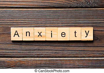 Anxiety word written on wood block. Anxiety text on wooden table for your desing, Top view concept