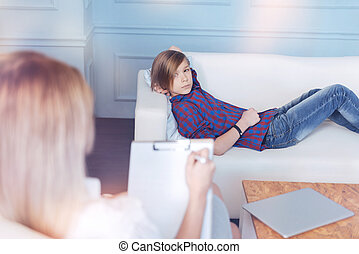 Anxious boy lying on couch in psychologist office