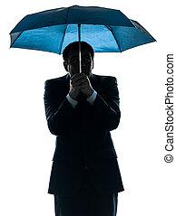 anxious business man under umbrella silhouette