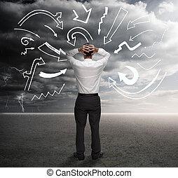 Anxious businessman looking at drawings of arrows