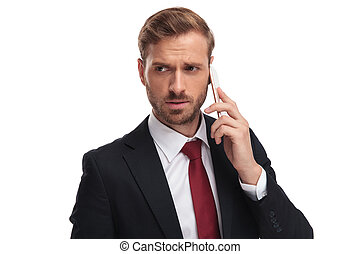 anxious businessman talking on the phone looks to side