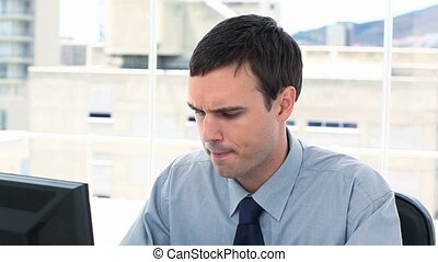 Anxious businessman working on his computer in a office
