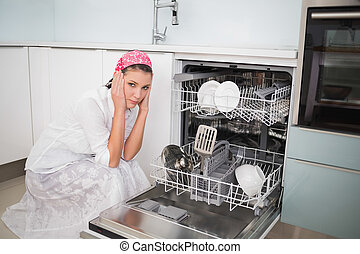 Anxious charming woman sitting next to dish washer in bright...