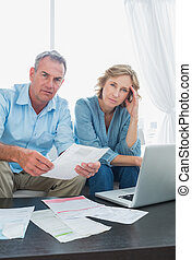 Anxious couple paying their bills online with laptop looking at camera at home in the living room