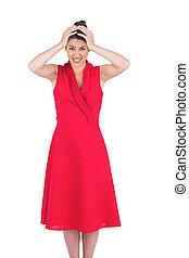 Anxious elegant brunette in red dress posing