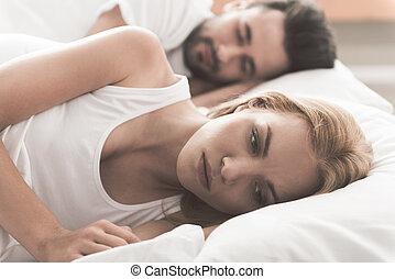 Anxious girl cannot sleep near her husband in bedroom