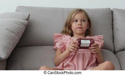 Anxious preteen girl in earphones sitting on sofa, holding...