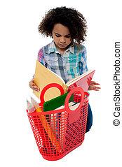 Anxious school girl reading a book