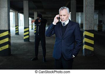 Anxious serious businessman making a call