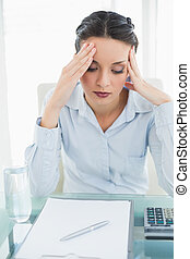 Anxious stylish brunette businesswoman holding her head in ...