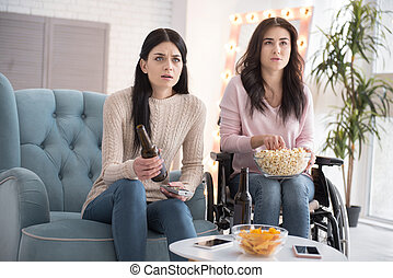 Anxious two sisters watching film