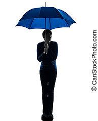 anxious woman holding umbrella silhouette