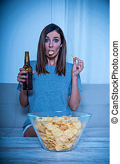 Anxious woman watching TV and eating