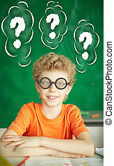 Any ideas? - Portrait of happy schoolboy in eyeglasses...