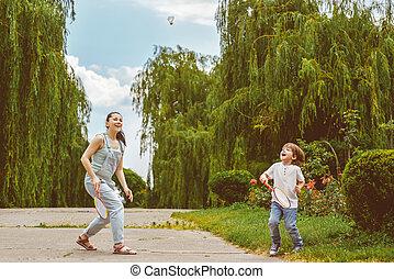 anya fiú, játék badminton, a parkban