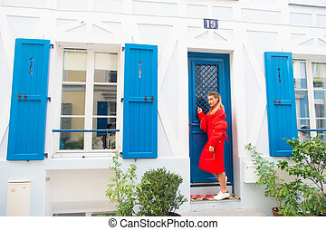 Anybody home. Lady guest knocking door waits owner apartment let her enter. Woman stylish outfit stand near door entrance house picturesque street in Paris. Visiting friends on vacation or holidays
