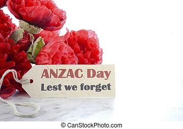 ANZAC Day, April 25, greeting with Lest We Forget and bunch of red silk poppies on white marble table, with copy space.