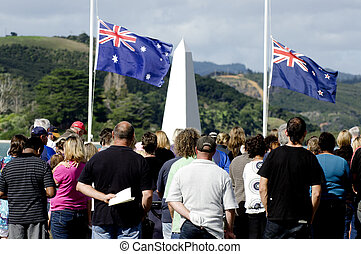 Crowd of people under the national flags of Australia and New Zealand during a National War Memorial Anzac Day services in New Zealand.