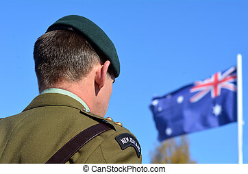 MANGONUI, NEW ZEALAND - APRIL 25 2014: New Zealand Army officer stands under New Zealand flag during the National War Memorial service.
