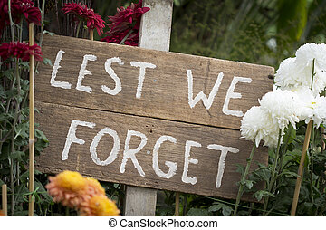 """ANZAC saying """"Lest We Forget"""" on Wooden Sign in Garden"""