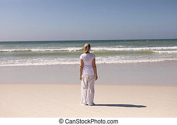 anziano, standing, vista, retro, donna, spiaggia