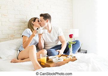 apaixonado, par beija, enquanto, brindar, xícaras café, cama