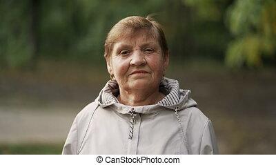 aparat fotograficzny., portret, park., patrząc, kobieta, sędziwy, kaukaski, piękny, jesień, babcia, uśmiechanie się