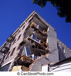 Apartment building after earthquake against clear blue sky