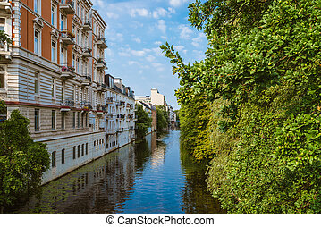 apartment buildings on bank of river or canal in residential district of Hamburg Eppendorf, Germany on sunny day
