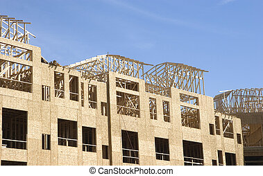 A new apartment complex being framed with wood and plywood lumber