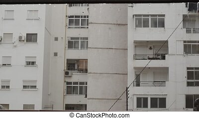 Apartment building with white facade and empty balconies, view in the rain