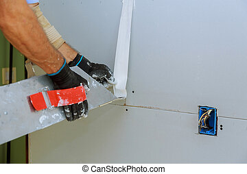 apartment interior construction worker plastering gypsum board wall