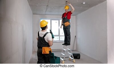 Apartment repair in draft room - a man worker standing in front of the camera and passes drill to another