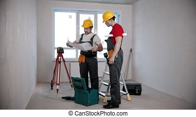 Apartment repair - two men workers opening up an apartment plan and looking at it