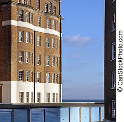 apartments or flats by the sea with garage in front. brick tower block building in england