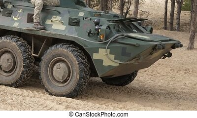 APC with big tires moving forward with military men in...