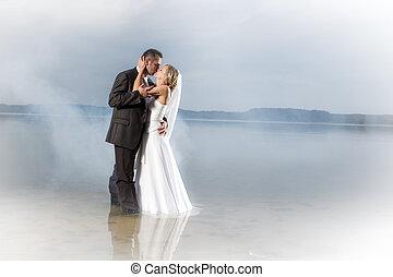 apenas casado, pareja joven, en, un, brumoso, lago