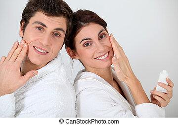 aplicando, par, jovem, rosto, seu, moisturizer