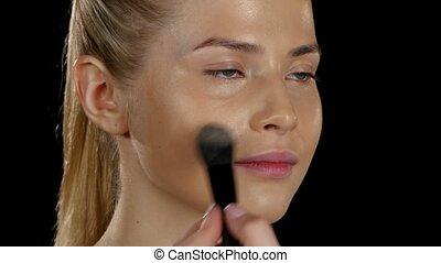 Aplication foundation. make up. Black. Closeup