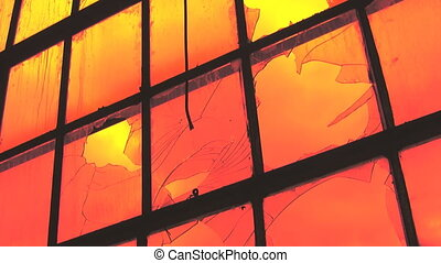 A large window at an abandoned factory. Looking out at orange timelapse clouds.