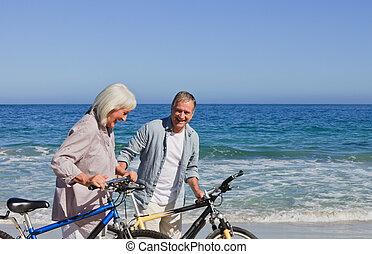 aposentado par, com, seu, bicicletas, praia
