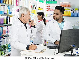 apotheker, gebruik, telefoon, terwijl, kijken naar, collega's, het gebruiken computer
