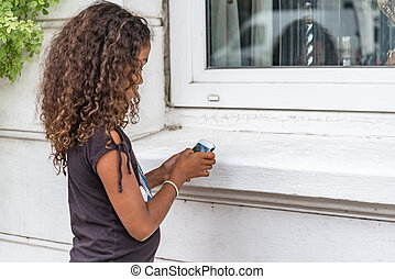 App game playing child with smartphone outside - Young girl...