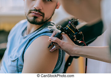 Apparat for tattoo. Attentive tattoo artist gently touching skin of her client with tattoo machine while he looking at this process